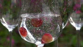 Las uvas caen en un vidrio