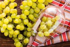 Las uvas en la copa de vino y el manojo de uvas en la tabla Fotos de archivo libres de regalías