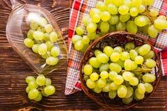 Las uvas en la copa de vino y en la cesta en la tabla de madera Imágenes de archivo libres de regalías