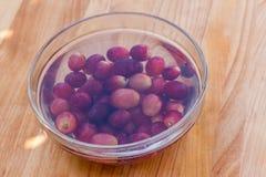 Las uvas rojas en agua sirvieron en bol de vidrio en tabla de cortar de madera Fotografía de archivo libre de regalías