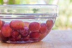 Las uvas rojas en agua sirvieron en bol de vidrio en tabla de cortar de madera Imágenes de archivo libres de regalías