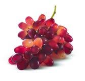 Las uvas rojas no agrupan ninguna hoja aislada en el fondo blanco Imagen de archivo
