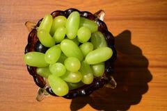 Las uvas verdes arreglaron en un bol de vidrio para la dieta sana y la buena salud foto de archivo libre de regalías