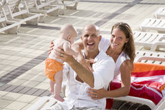 Las vacaciones de familia, se relajan en sillas de salón de la cubierta de la piscina Imagen de archivo libre de regalías