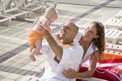 Las vacaciones de familia, se relajan en sillas de salón de la cubierta de la piscina Imagen de archivo