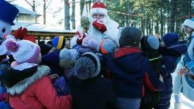 Las vacaciones de invierno para los niños, la Navidad en la ciudad, Santa Claus están llamando a los niños, muchos niños recolect almacen de metraje de vídeo