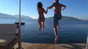 Las vacaciones de verano, los amigos felices con comienzo corriente saltan en el mar del embarcadero almacen de metraje de vídeo