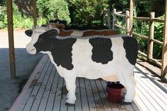 Las vacas falsas se alinearon con el cubo para el tomilk de los niños Imagen de archivo