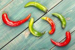 Las vainas de las pimientas de chile rojas y verdes en un fondo de madera Fotografía de archivo libre de regalías