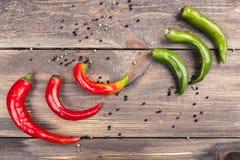 Las vainas de las pimientas de chile rojas y verdes en un fondo de madera con las bolas de la especia Fotografía de archivo libre de regalías