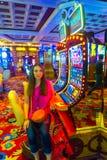 Las Vegas Amerikas förenta stater - Maj 06, 2016: Den unga kvinnan som poserar på enarmade banditer i det Excalibur hotellet och Royaltyfri Bild