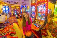 Las Vegas Amerikas förenta stater - Maj 06, 2016: Den unga kvinnan som poserar på enarmade banditer i det Excalibur hotellet och Royaltyfri Foto
