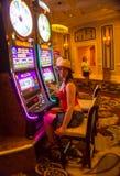 Las Vegas Amerikas förenta stater - Maj 06, 2016: Den unga kvinnan som poserar på enarmade banditer i det Excalibur hotellet och Royaltyfri Fotografi