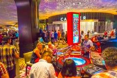 Las Vegas Amerikas förenta stater - Maj 06, 2016: Folket som spelar på enarmade banditer i det Excalibur hotellet och Arkivbilder