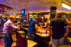 Las Vegas Amerikas förenta stater - Maj 06, 2016: Folket som spelar på enarmade banditer i det Excalibur hotellet och Royaltyfri Foto