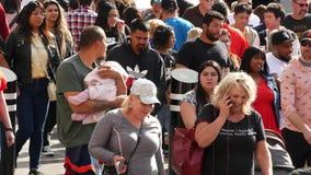 LAS VEGAS, NEVADA USA - 7 MAR 2020: People on pedestrian walkway. Multicultural men and women walking on city promenade