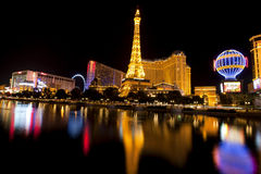 Las Vegas Nightlife along the famous strip. Nightlife along the famous Las Vegas Strip with the Flamingo, High Roller Ferris Wheel, Bally's Casinos reflecting in Stock Photo