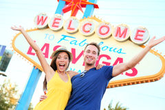 Las vegas people - couple happy cheering by sign. Welcome to Las Vegas sign billboard and excited cheerful young multiracial couple having fun on the strip Stock Image