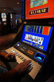 Las Vegas Slot Machine. A man plays a $1 US slot machine in Las Vegas Royalty Free Stock Photo
