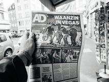2017 Las Vegas Strip shooting algemeen dagblad newspaper. PARIS, FRANCE - OCT 3, 2017: Man buyingDutch algemeen dagblad newspaper with socking title and photo at Stock Photo