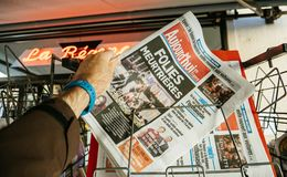 2017 Las Vegas Strip shooting aujord`hui french newspaper. PARIS, FRANCE - OCT 3, 2017: Man buying Aujord`hui French newspaper with socking title and photo at Stock Photo
