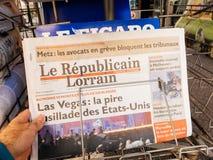 2017 Las Vegas Strip shooting Le Republicain Lorrain newspaper. PARIS, FRANCE - OCT 3, 2017: Man buying Le republicai Lorrain newspaper with socking title and Stock Photo