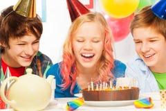 Las velas adolescentes jovenes del soplo de la muchacha con los amigos ríen Fotografía de archivo