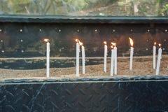 Las velas ardientes blancas se colocan en la arena imágenes de archivo libres de regalías