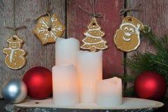 Las velas blancas cerca de una pared de madera roja con las galletas y el abeto de la Navidad ramifican Fotos de archivo libres de regalías