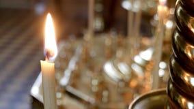 Las velas de Defocus son quemaduras en una iglesia ortodoxa contra la pared del alto templo almacen de video