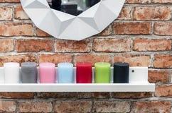 Las velas de diversos colores están en el estante blanco en el interior del desván foto de archivo