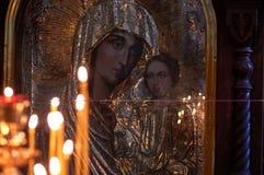Las velas de la iglesia se reflejan en el icono de la madre de dios Imagen de archivo