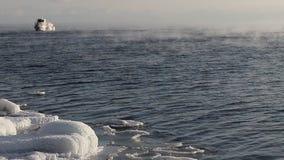 Las velas de la nave en el lago Baikal que flota de helada a lo largo de la costa helada en enero almacen de metraje de vídeo