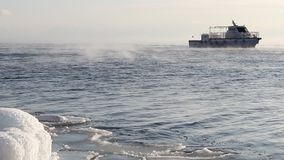 Las velas de la nave en el lago Baikal que flota de helada a lo largo de la costa helada en enero metrajes