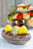 Las velas de Pascua en el cuenco de cerámica adornado con las codornices empluman Foto de archivo libre de regalías