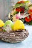 Las velas de Pascua en el cuenco de cerámica adornado con las codornices empluman Fotos de archivo libres de regalías