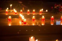 Las velas del rezo encienden para arriba la oscuridad en una iglesia foto de archivo