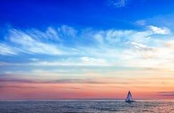 Las velas del velero debajo del sol poniente fotografía de archivo libre de regalías