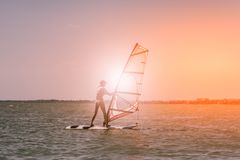 Las velas delgadas atléticas jovenes de la muchacha en a windsurf tablero en el mar abierto el vacaciones de verano en el centro  imagen de archivo