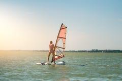 Las velas delgadas atléticas jovenes de la muchacha en a windsurf tablero en el mar abierto el vacaciones de verano en el centro  foto de archivo libre de regalías