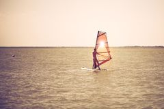 Las velas delgadas atléticas jovenes de la muchacha en a windsurf tablero en el mar abierto el vacaciones de verano en el centro  fotos de archivo libres de regalías