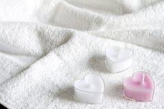 Las velas en el cuerpo blanco del extracto de la toalla cuidan el balneario Foto de archivo libre de regalías