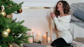 Las velas encendidas, muchacha hacen un deseo, soplan hacia fuera una vela, sentándose por la chimenea cerca del árbol de navidad almacen de video