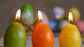 Las velas hicieron en la forma del huevo de Pascua Velas ardientes verde, anaranjado, amarillo Velas de los huevos de Pascua y Pa almacen de metraje de vídeo