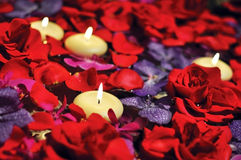 Las velas lujosas flotan en la cama de rosas romántica Foto de archivo libre de regalías