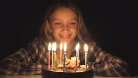 Las velas que soplan en noche, niño de la fiesta de cumpleaños del niño celebran con la torta en oscuridad imágenes de archivo libres de regalías