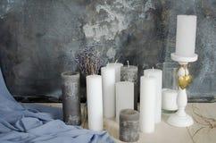 Las velas y la lavanda florece en un fondo de la pared gris Fotos de archivo libres de regalías