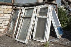 Las ventanas viejas en un marco de madera con la pintura blanca lamentable y mentira de cristal quebrada en un montón en la desca Foto de archivo libre de regalías