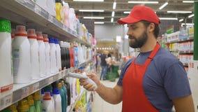 Las ventas clerk en código de barras de los limpiadores de la exploración del uniforme del rojo en supermercado almacen de video