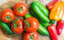 Las verduras crudas en cocina cortaron el tablero, visión superior Imagen de archivo libre de regalías